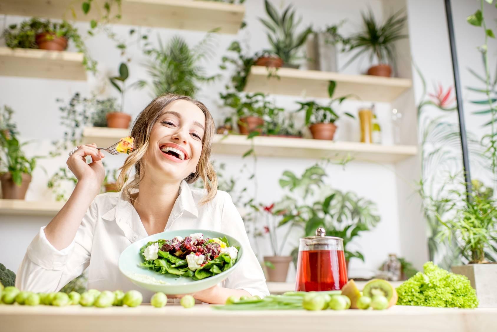 Jak się zdrowo odżywiać, by być szczupłą i zdrową? Na czym polega walka z otyłością? Młoda kobieta je sałatkę.
