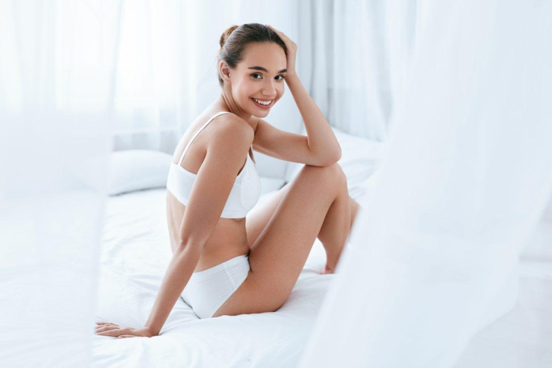 Założyć stanik czy zdjąć? Spać w majtkach czy nie? Jaką bieliznę wybierać na co dzień? Uśmiechnięta kobieta w białej bawełnianej bieliźnie siedzi na łóżku osłonięta zasłonką z baldachimu.