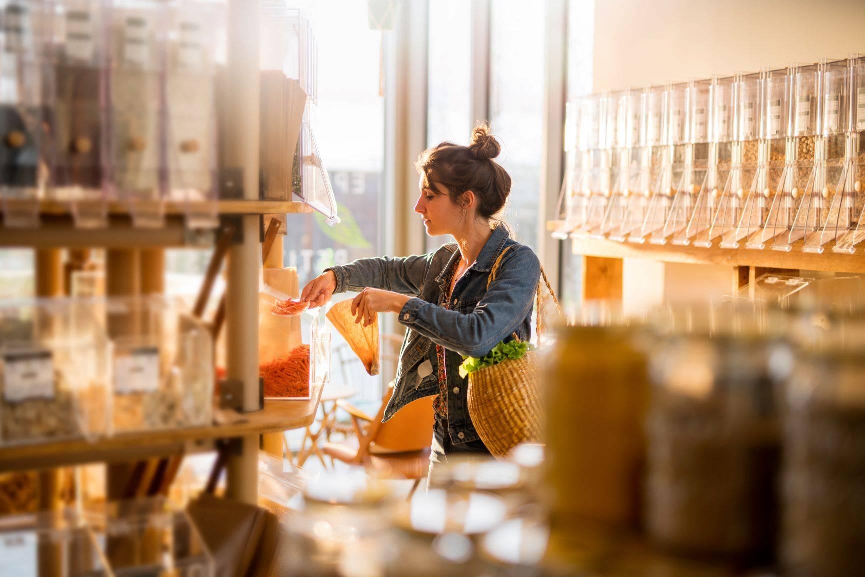 Planowanie zakupów, czyli jak nie marnować jedzenia? Kobieta nakłada do papierowej torebki odmierzoną ilość kaszy.