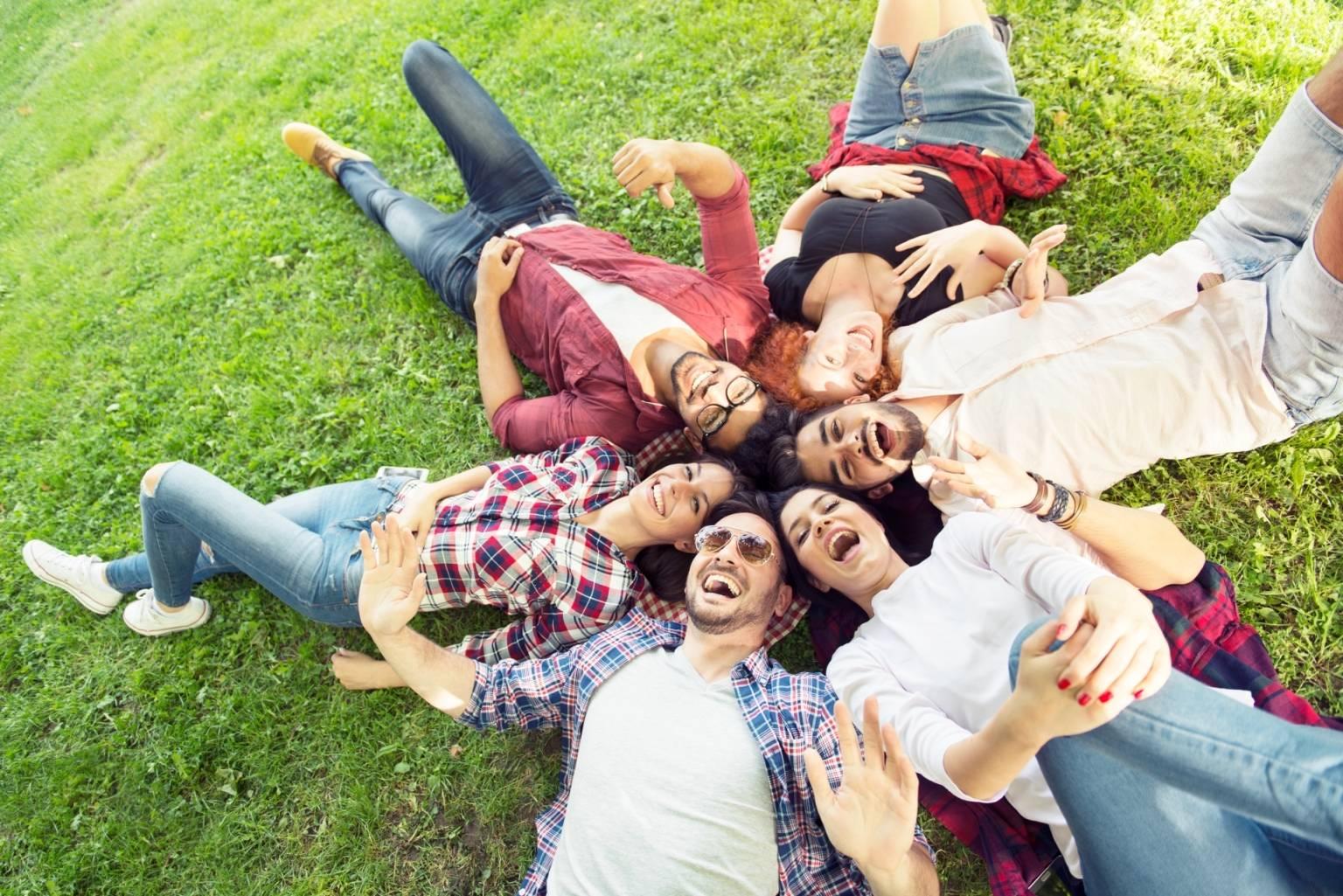 Joga śmiechu - na czym polega śmiechoterapia, czyli terapia śmiechem i czym jest gelatologia? Grupa młodych ludzi śmieje się, leżąc obok siebie w kółku na trawie.