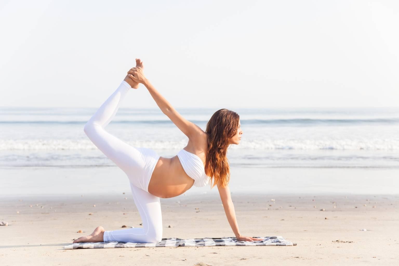 Medycyna chińska na dolegliwości w ciąży. Kobieta ciężarna ćwiczy jogę na macie na plaży nad brzegiem morza.