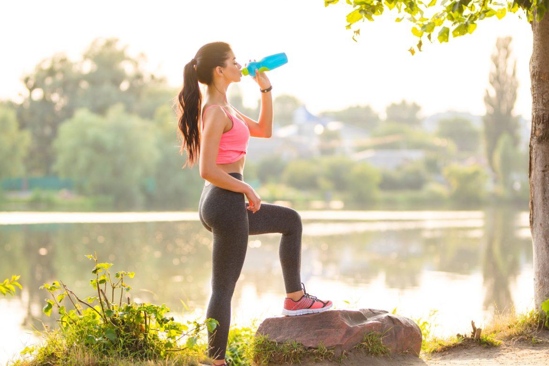Prawidłowa postawa - jak zadbać o ładną sylwetkę? Biegaczka odpoczywa w przerwie od treningu nad jeziorem, pijąc wodę z bidonu.