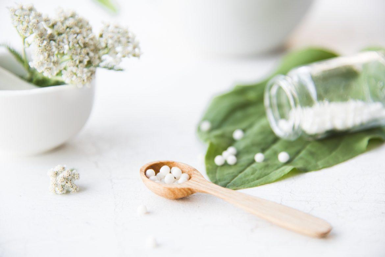 Kalium carbonicum - na co pomaga lek homeopatyczny? Granulki homeopatyczne, wysypujące się z fiolki, na zielonym liściu i drewnianej łyżce.