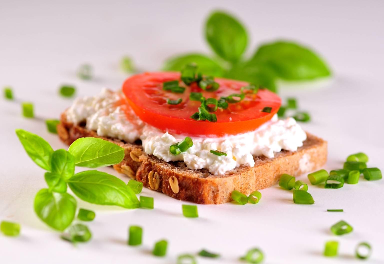 Dieta na odporność - unikaj produktów zawierających gluten. Kromka ciemnego pieczywa z twarożkiem, pomidorem, szczypiorkiem i listkami bazylii leży na białym blacie.