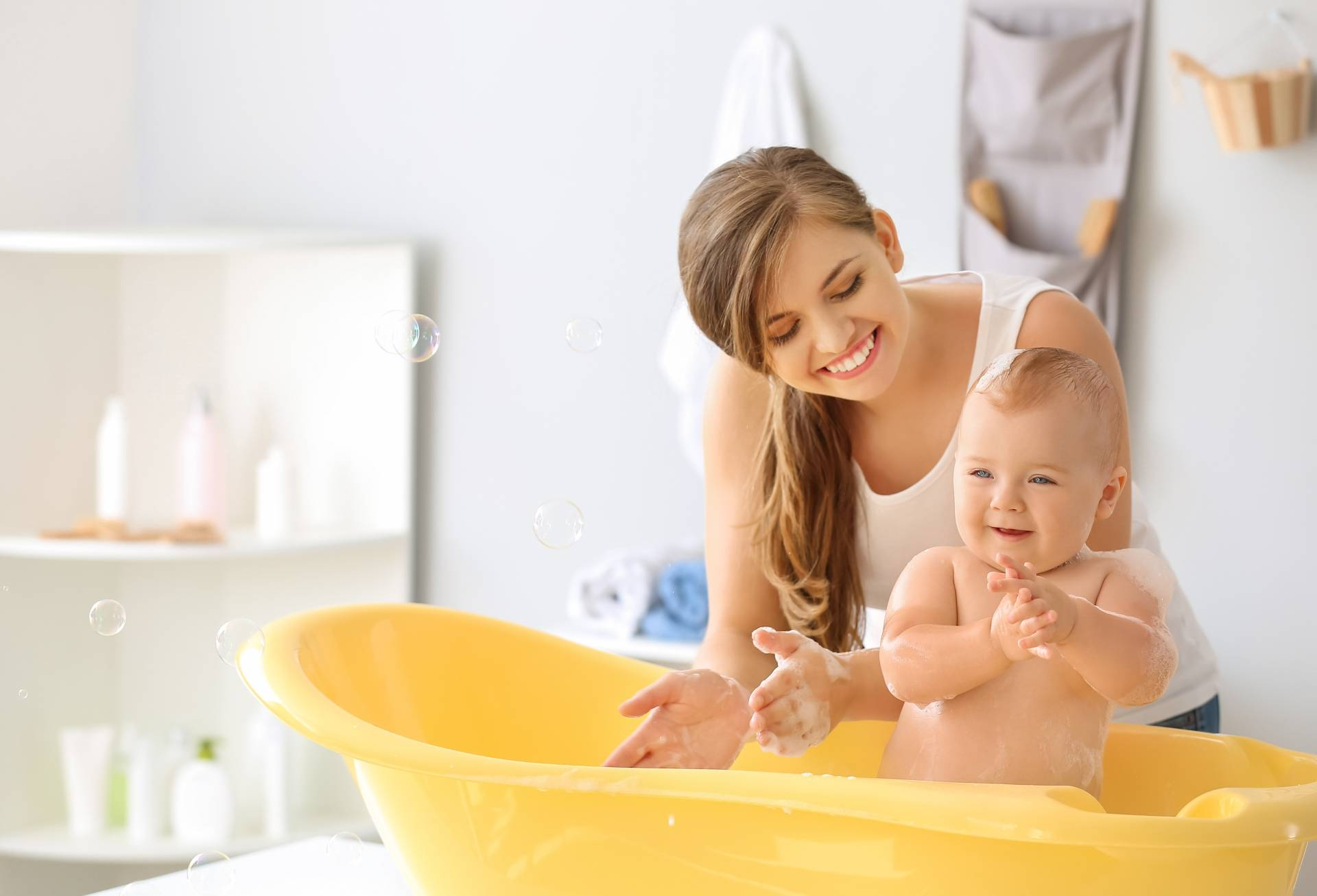 Kąpiele lecznicze na atopowe zapalenie skóry u dzieci i dorosłych. Mama kąpie niemowlę w żółtej wanience.