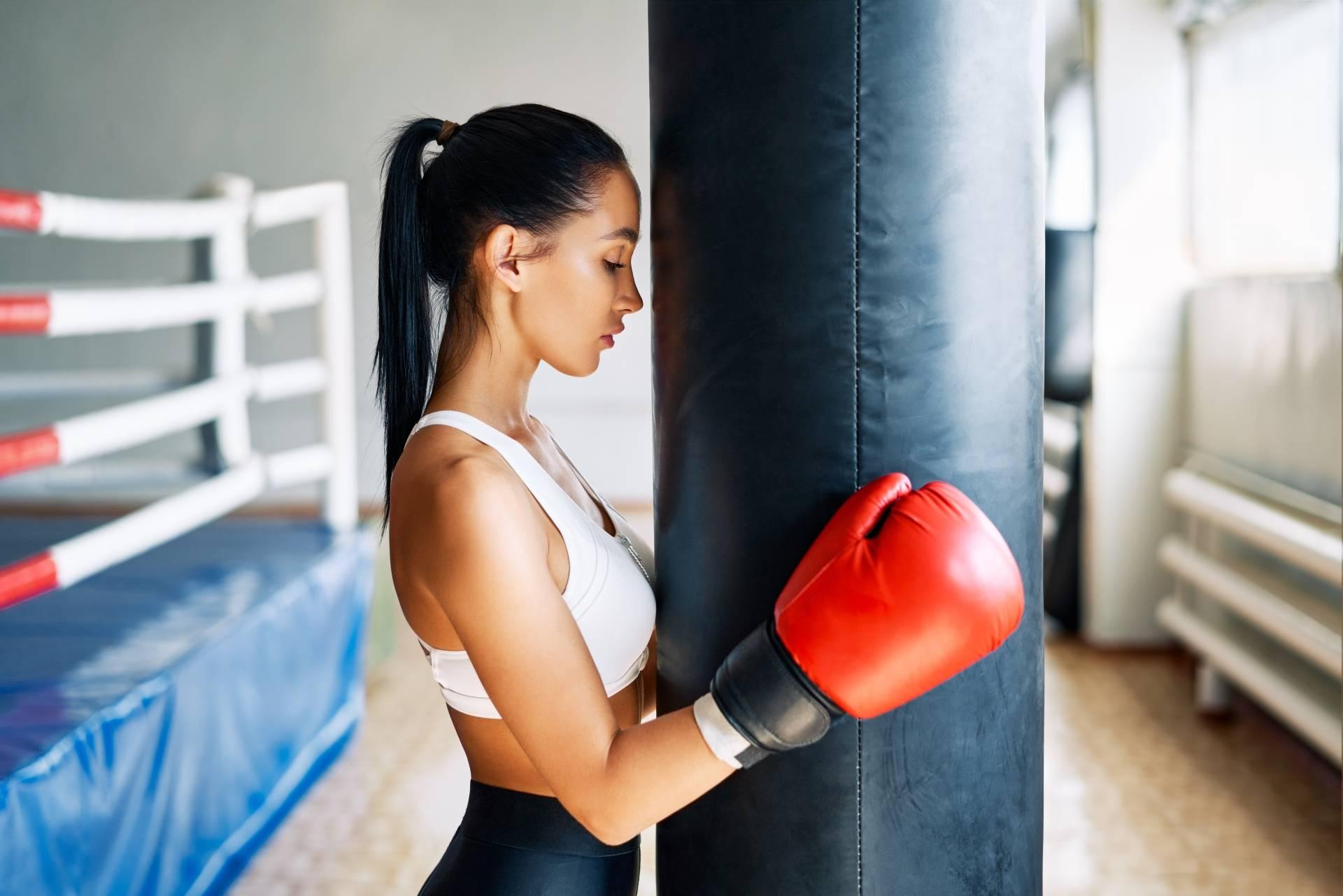 Myśl jak sportowiec - jak czerpać mądrość z psychologii sportu? Młoda atrakcyjna kickbokserka opiera się głową o worek treningowy i obejmuje go rękawicami.