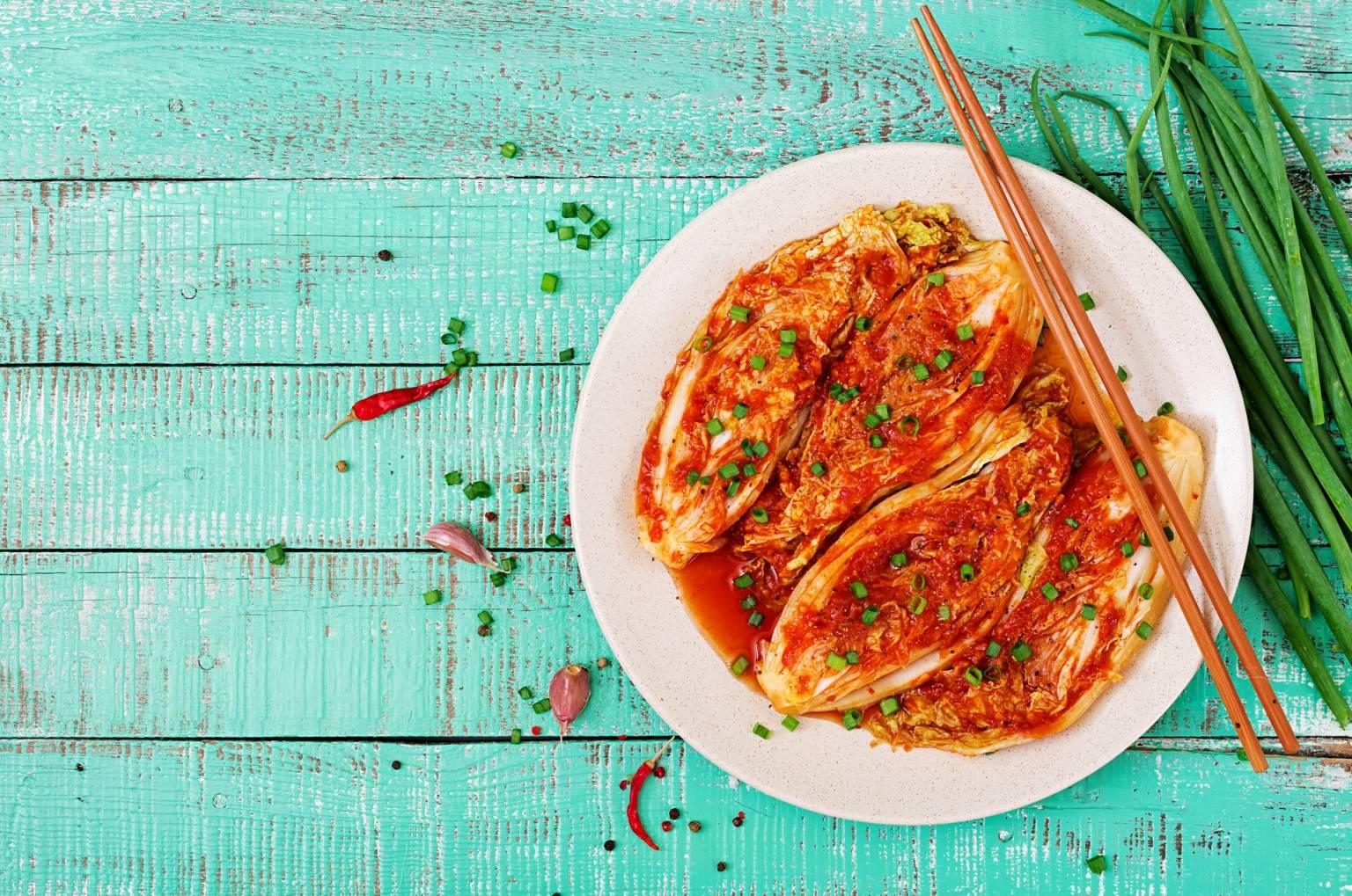 Tradycyjny przepis na kimchi. Jak zrobić kiszoną kapustę pekińską z warzywami i przyprawami? Kimchi na talerzu z pałeczkami leży na niebieskim starym drewnianym stole.