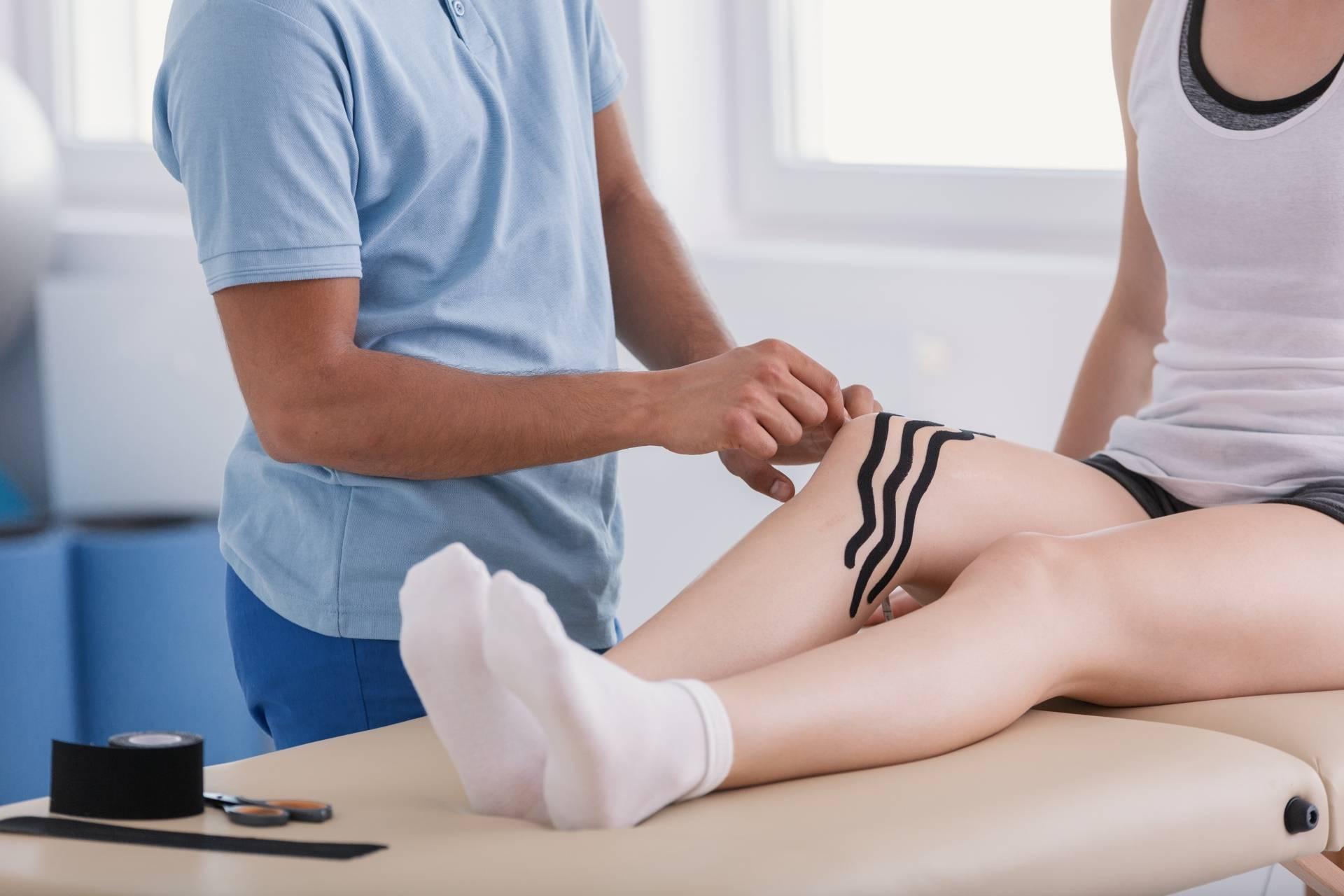 Kinesiotaping: fizjoterapeuta przykleja pacjentce tejpy na kolano.