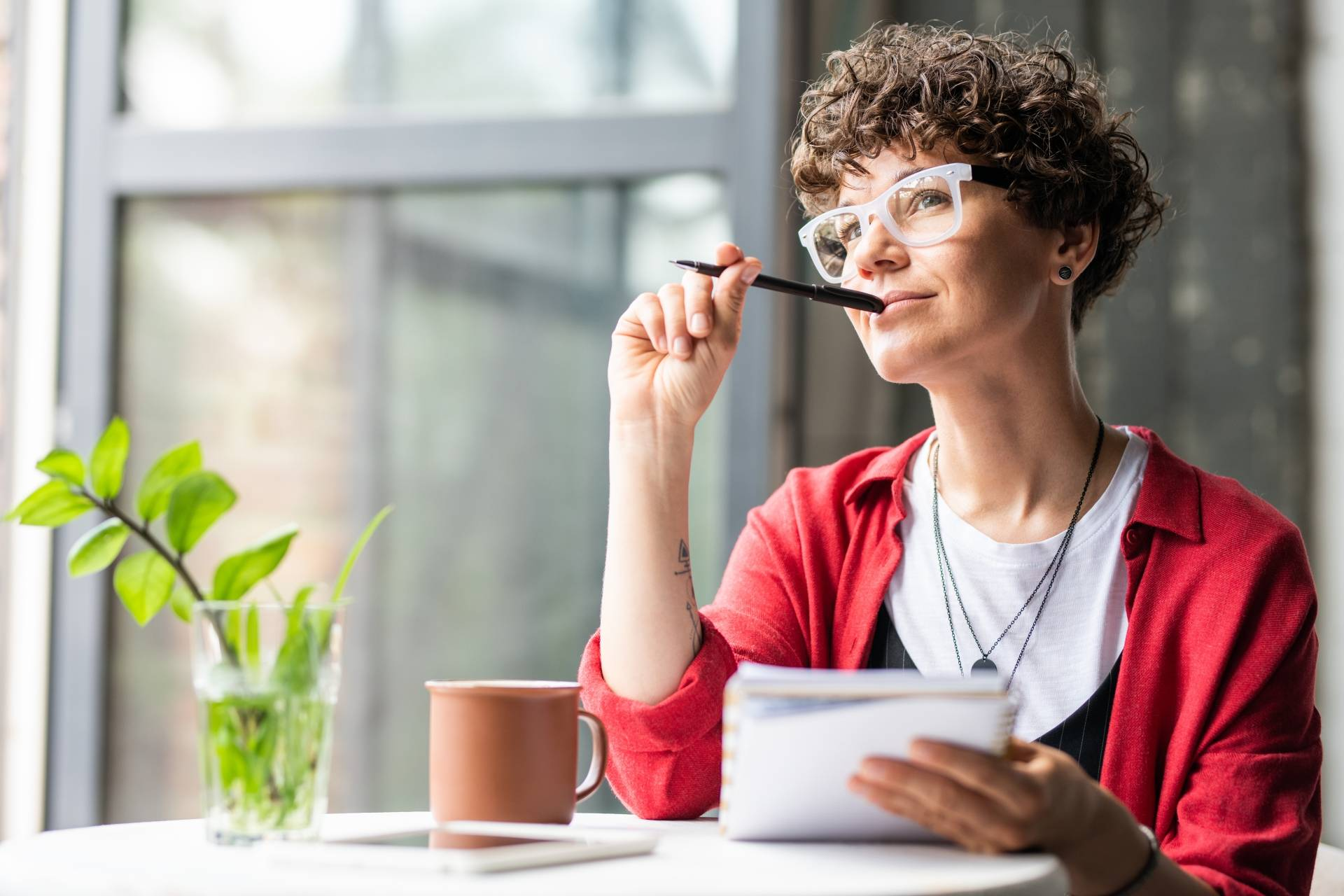 Kintsugi - jak pozbierać się w całość? Młoda kobieta w czerwonej koszuli, krótkich kręconych włosach i okularach w jasnej rogowej oprawie zastanawia się co napisać w dzienniku.