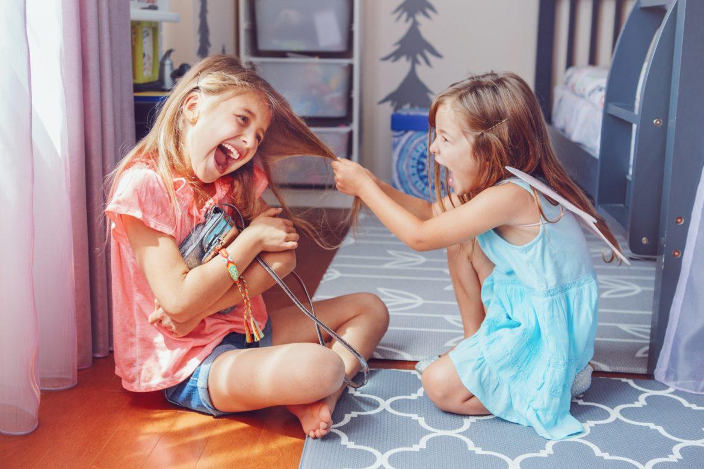 Kłótnie między rodzeństwem - jak im zapobiegać? Siostry kłócą się u siebie w pokoju - jedna ciągnie drugą za włosy.