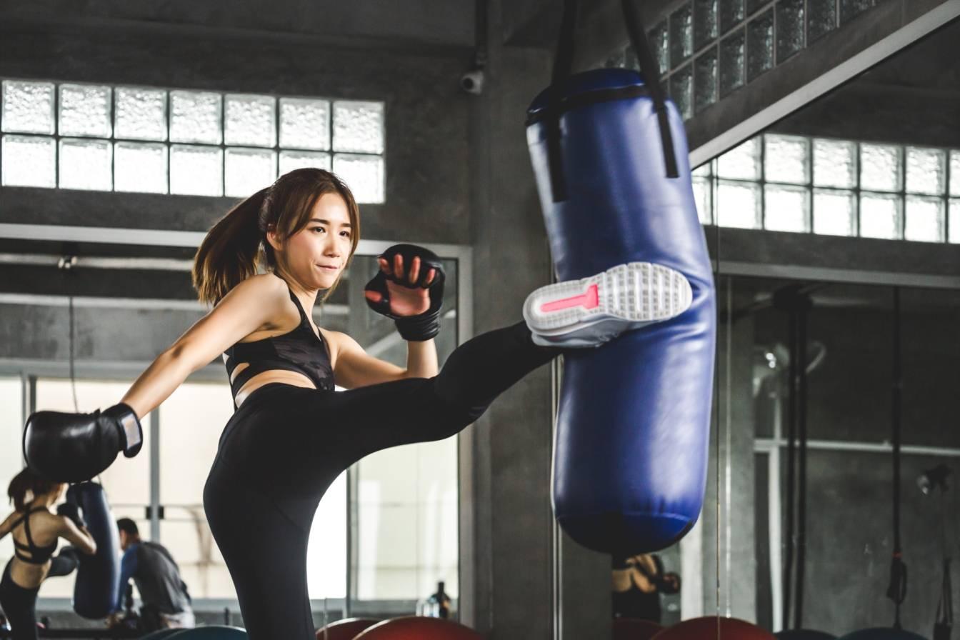 Boks kobiecy - jak trenować boks? Kobieta Azjatka kopie w worek treningowy w klubie bokserskim.