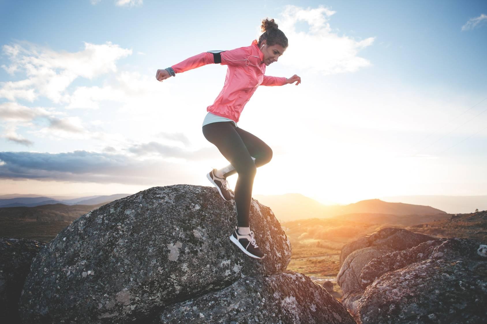 Sok z buraka - izotonik dla sportowców. Kobieta w sportowym stroju biegająca po górach i skałach o zachodzie słońca.