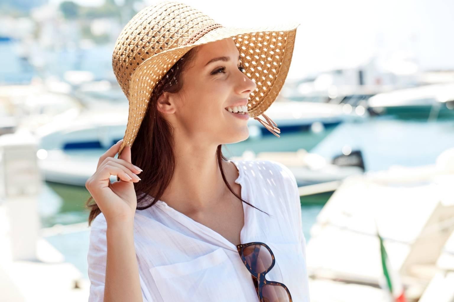 Uśmiechnięta kobieta w słomkowym kapeluszu stoi latem na molo. W jaki sposób śmiech wspiera odporność?