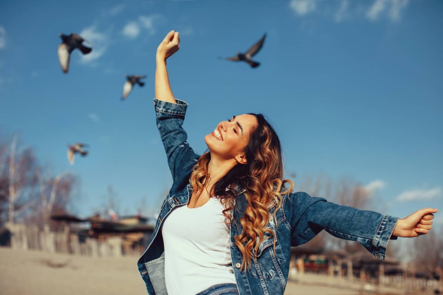 Czy sztuczne światło nam szkodzi? Szczęśliwa uśmiechnięta dziewczyna w białym topie i jeansowej kurtce cieszy się piękną pogodą, w tle latają ptaki.