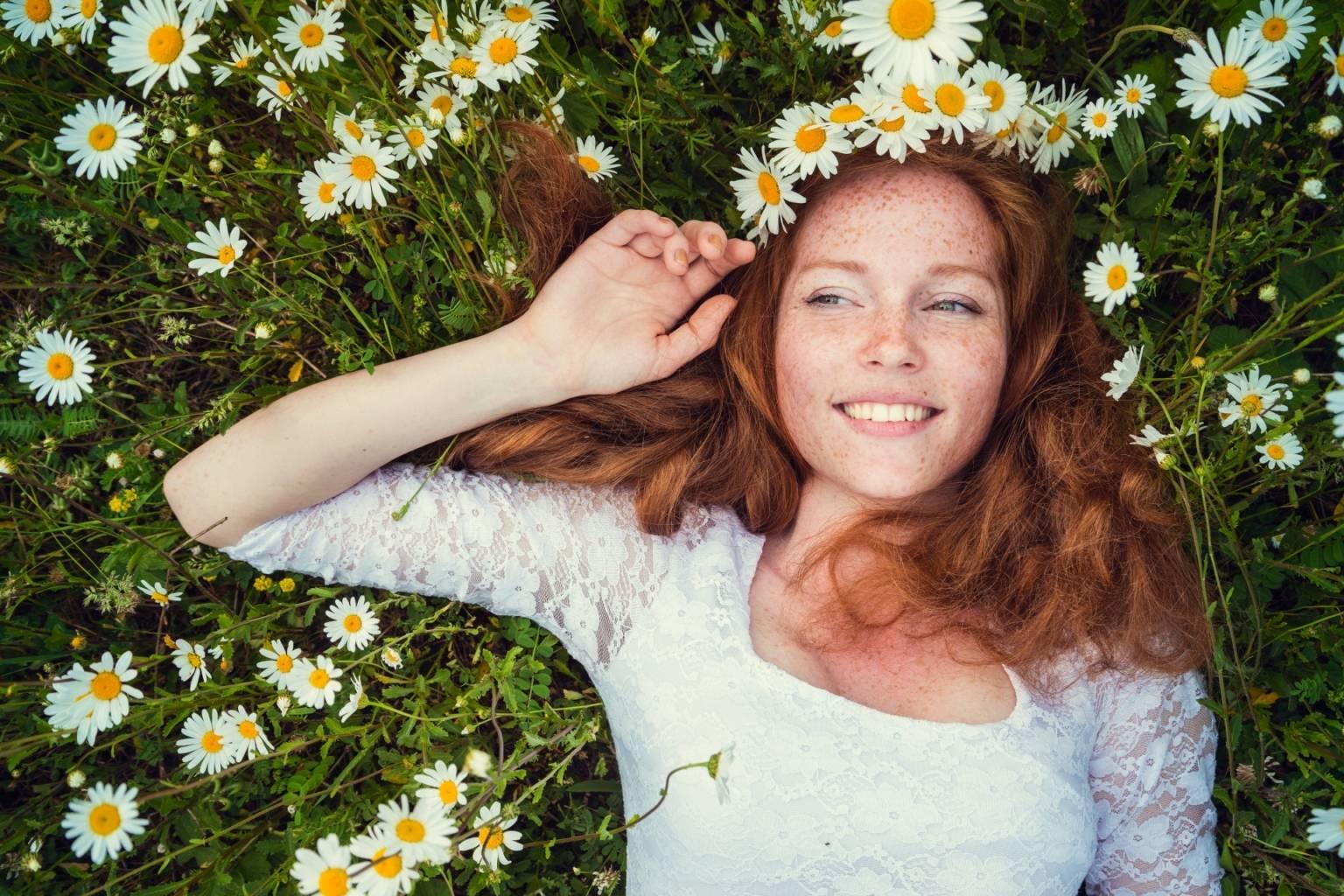 Rumianek - jakie ma właściwości? Rudowłosa kobieta leży na trawie pośród kwiatów rumianku, na głowie ma zapleciony rumiankowy wianek.