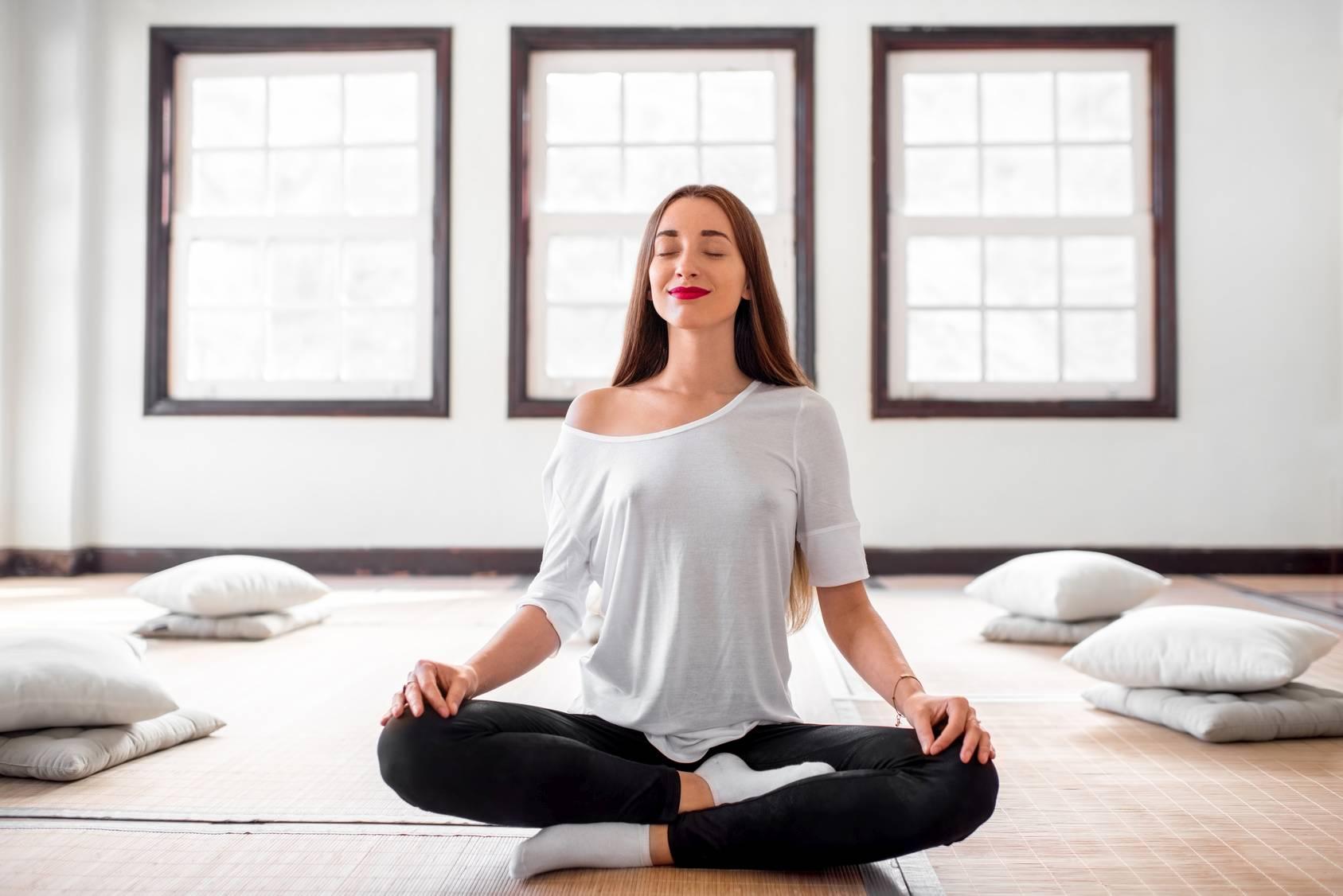 Joga twarzy - jak wykonywać ćwiczenia mięśni twarzy. Młoda kobieta ćwiczy jogę na sali.