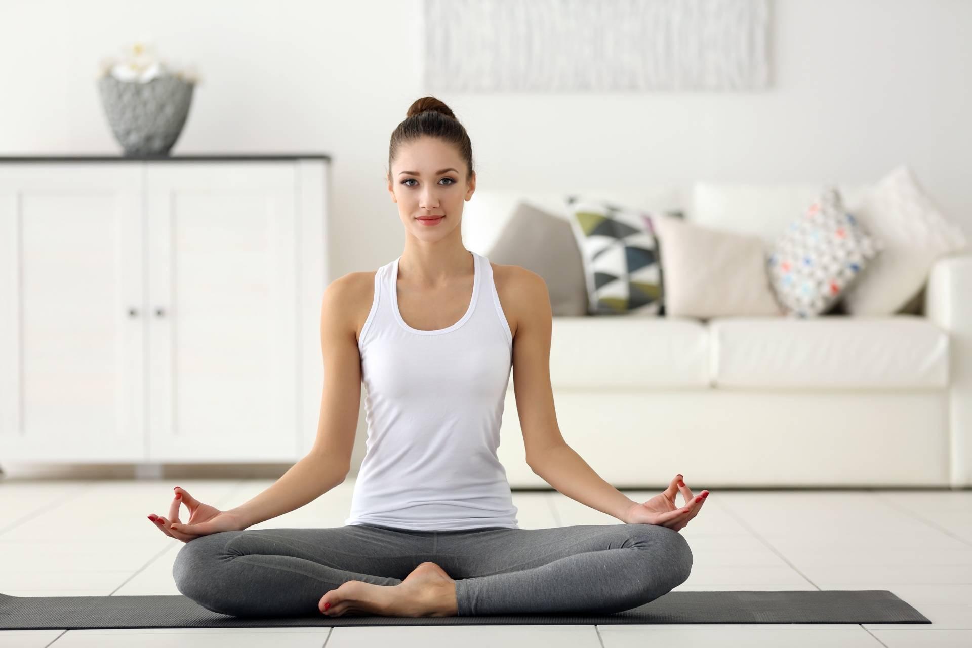Jak medytować? Młoda kobieta w białym topie i szarych legginsach siedzi na macie w salonie i medytuje.