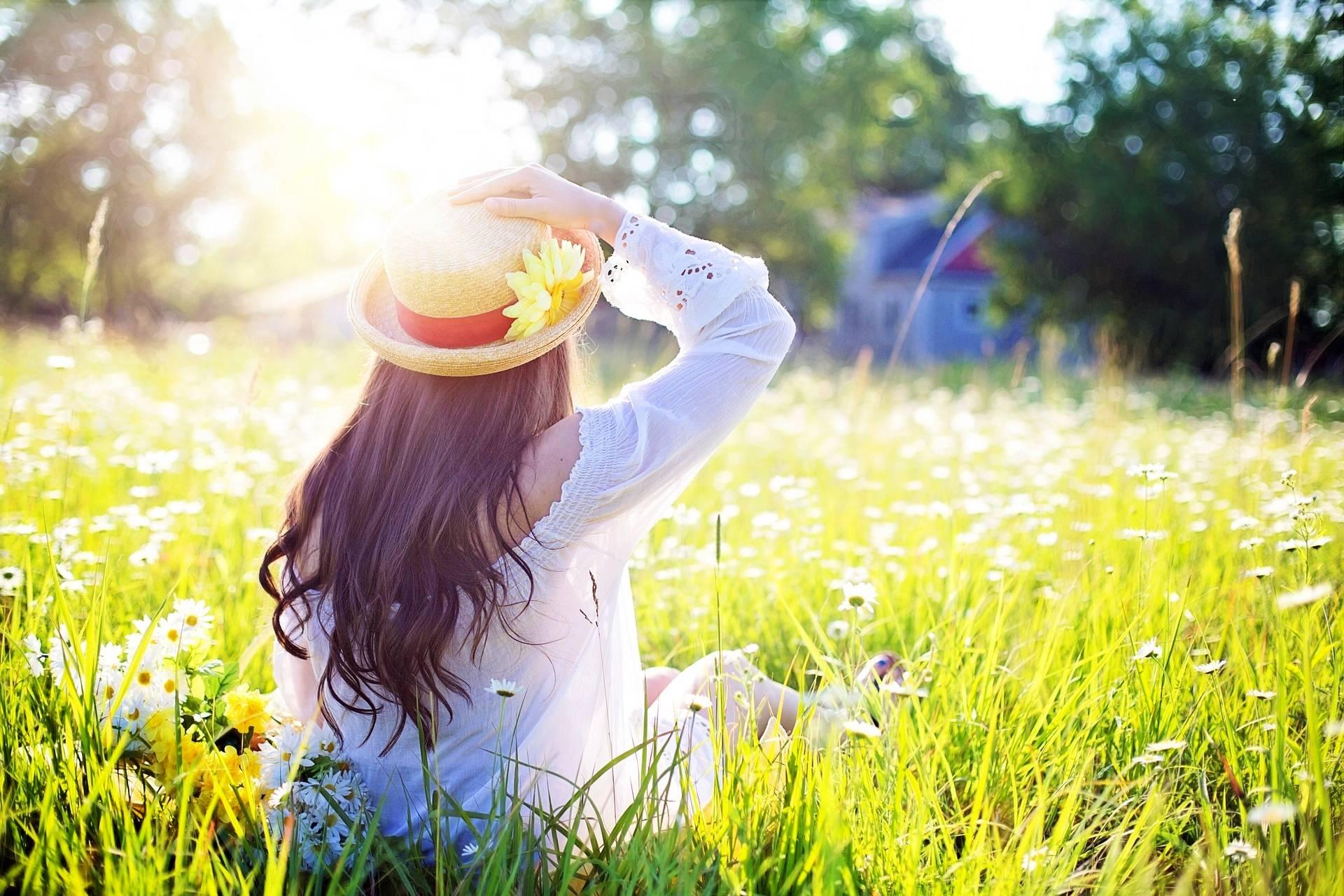 Naturalne domowe sposoby na ukąszenie osy, pszczoły, szerszenia lub muszki. Kobieta w słomkowym kapeluszu siedzi na łące.
