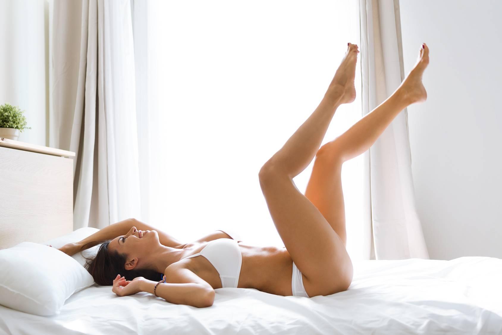 Opuchnięte nogi - jak z nimi walczyć? Młoda uśmiechnięta kobieta w białej bieliźnie leży na łóżku z uniesionymi nogami.