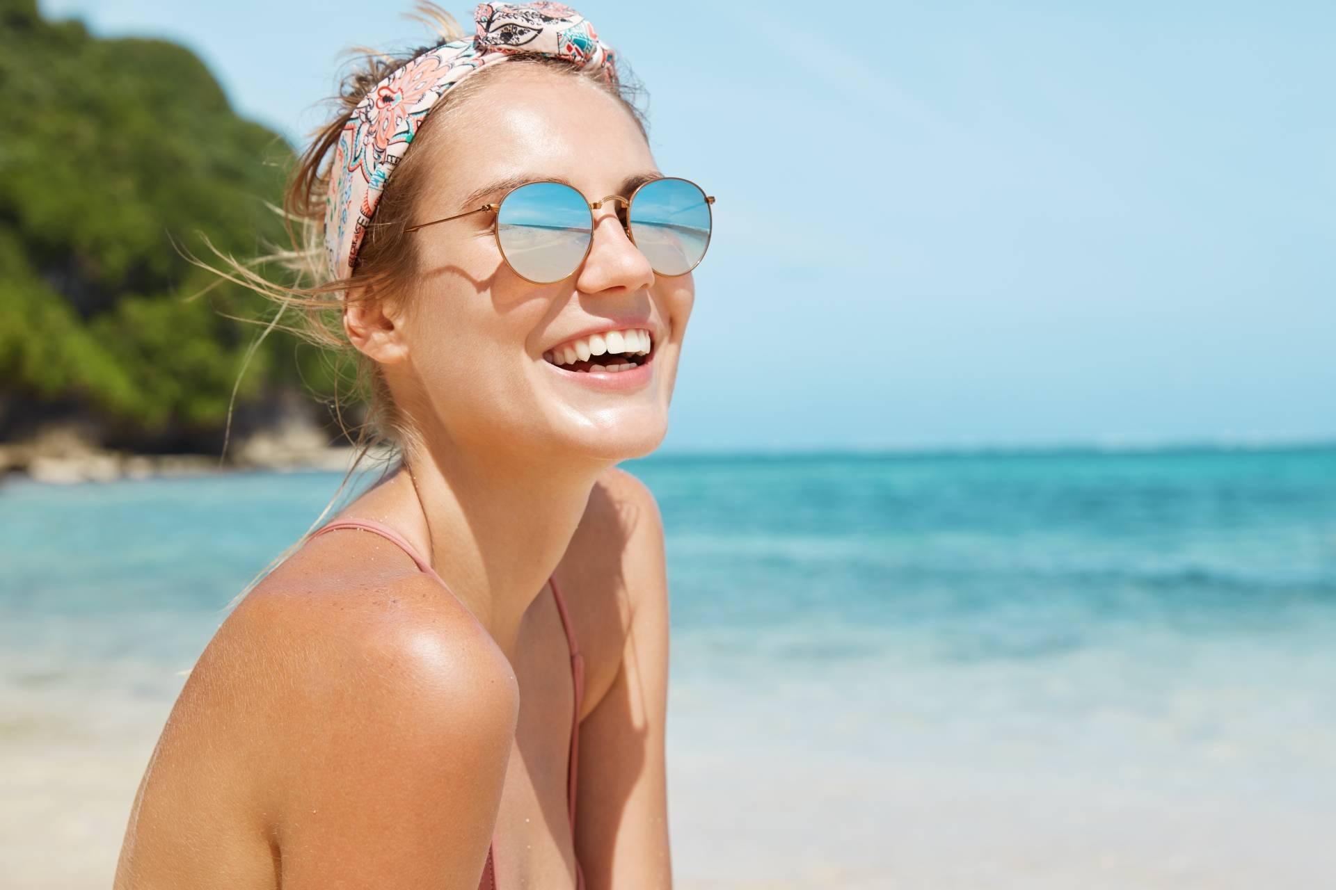 Opalanie przy problemach z cerą. Młoda dziewczyna opala się na plaży.