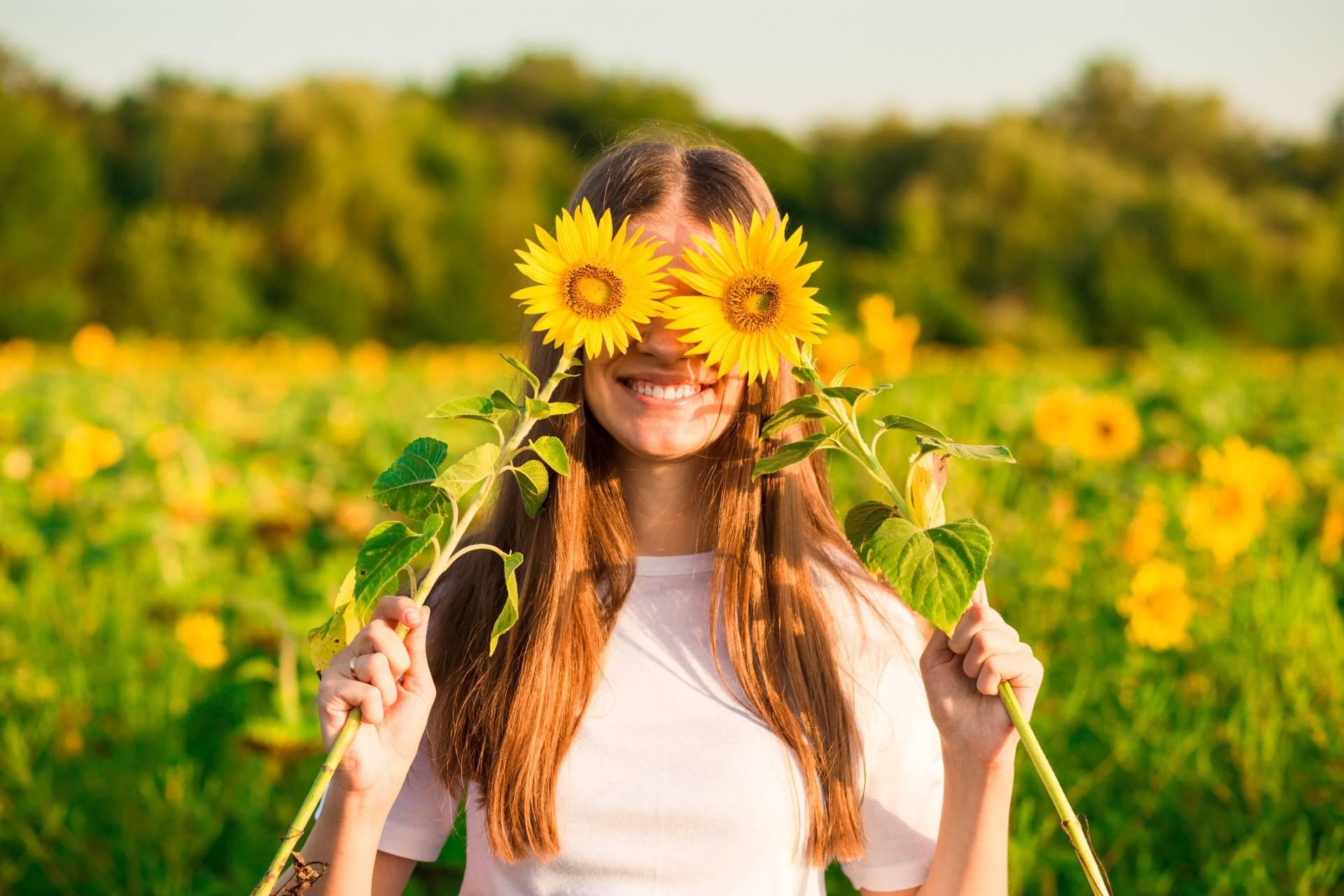 Alergia na pyłki - jak ją pokonać? Uśmiechnięta dziewczyna stoi w polu słoneczników, trzymając w ręku dwa zerwane słoneczniki - przykłada je do twarzy w miejsce oczu.