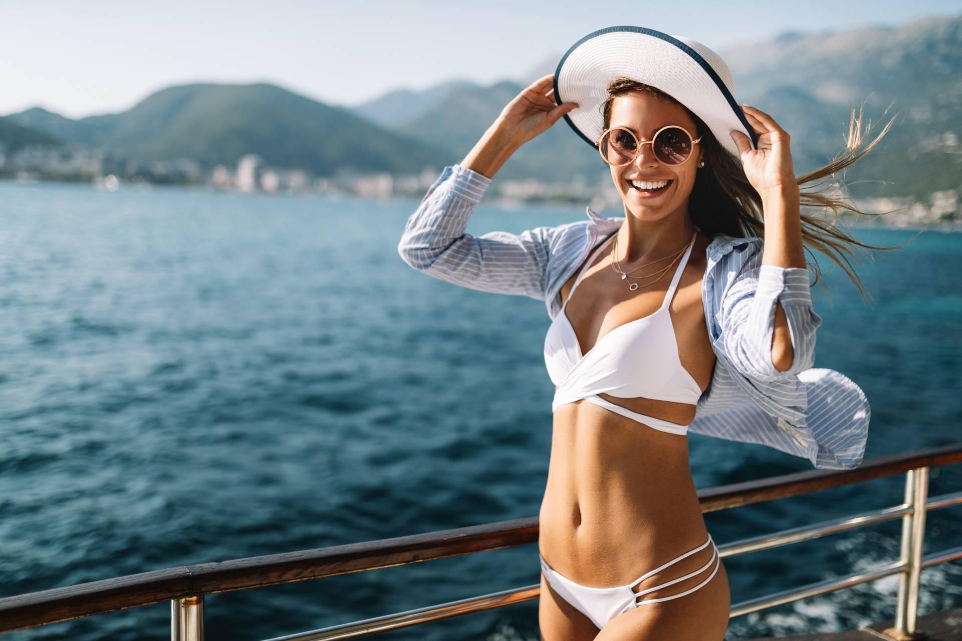 Przebarwienia na skórze. Jak ich uniknąć? Atrakcyjna kobieta w stroju kąpielowym i kapeluszu stoi na pomoście nad jeziorem.