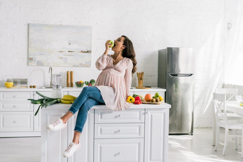 Zgaga w ciąży - jak sobie z nią poradzić? Kobieta w ciąży siedzi na blacie w kuchni je jabłko.