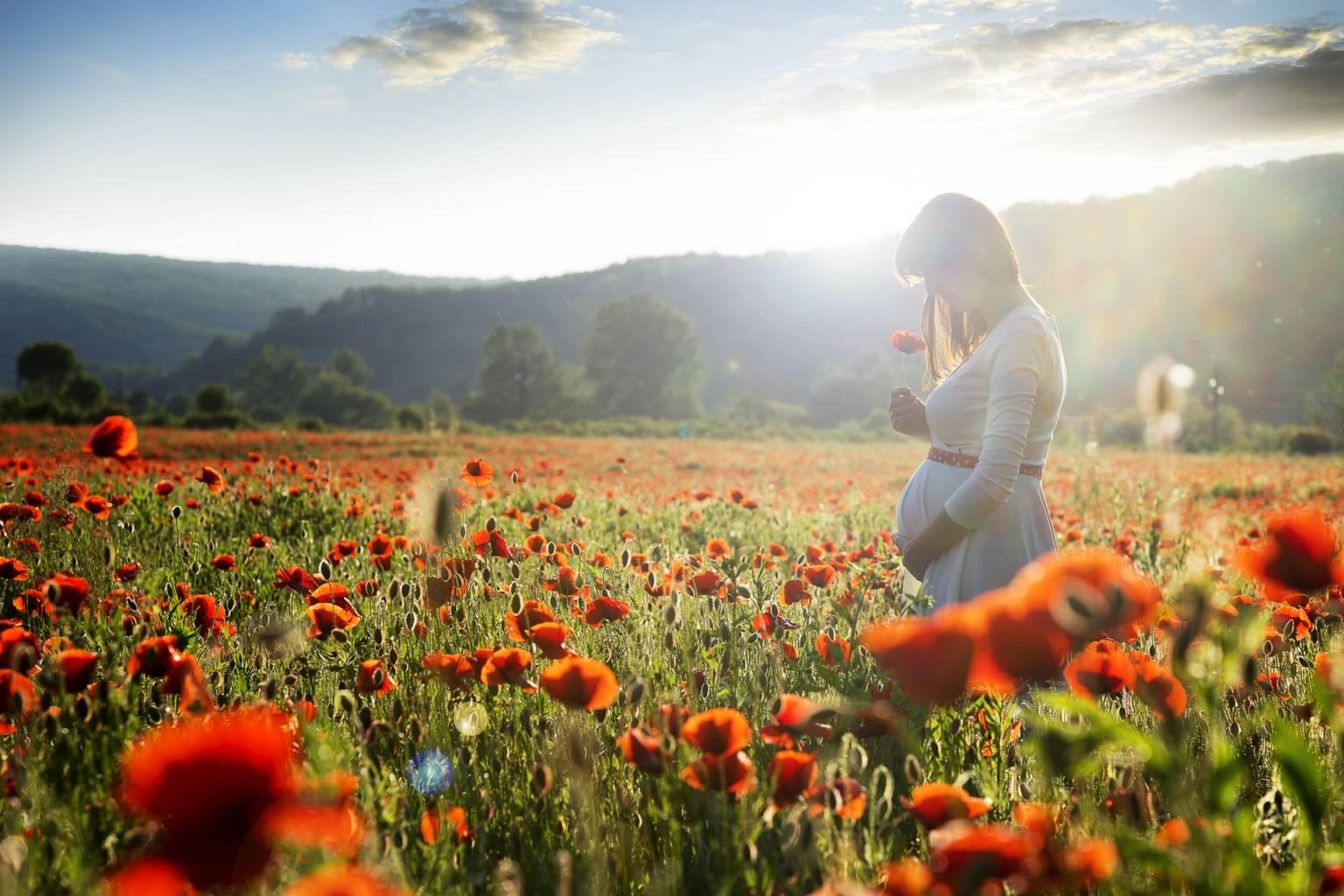 Leki homeopatyczne na dolegliwości w ciąży. Kobieta w ciąży spaceruje po łące pełnej maków.