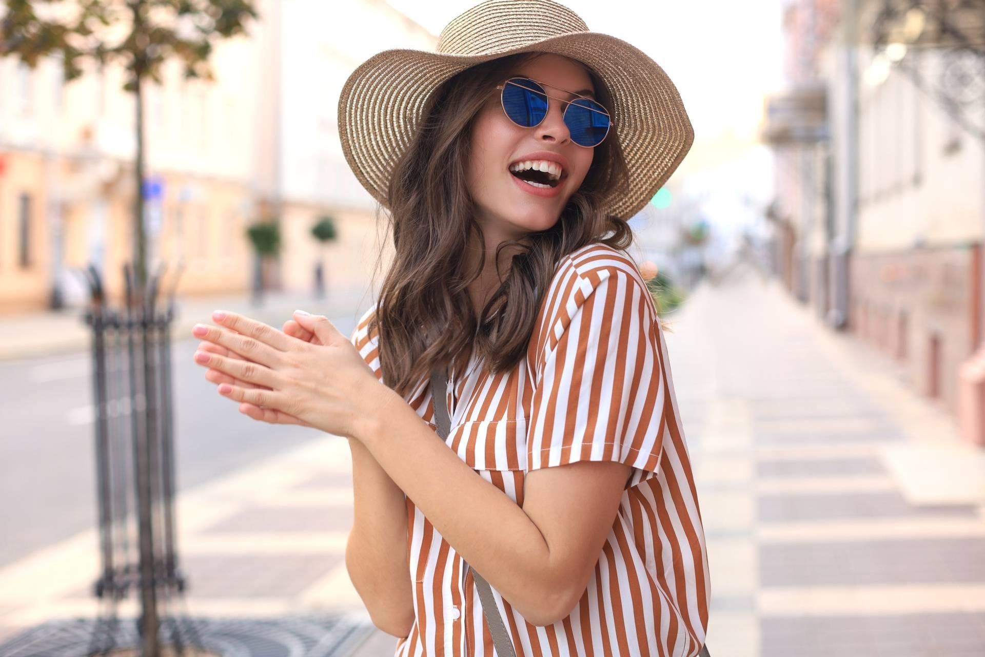 Jak dbać o oczy latem? Młoda atrakcyjna dziewczyna w okularach przeciwsłonecznych, białym kapeluszu i koszuli w paski stoi na ulicy i uśmiecha się.