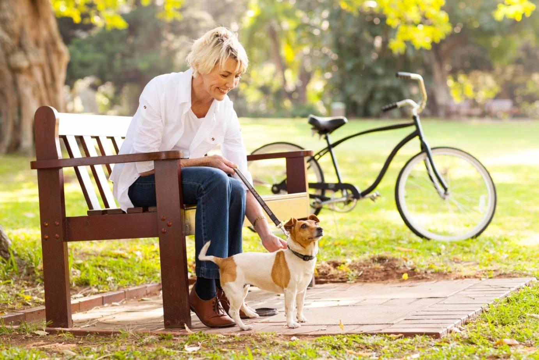 Homeopatia na menopauzę i okres przekwitania. Jakie są objawy klimakterium? Dojrzała kobieta siedzi na ławce w parku i głaszcze swojego psa, w tle stoi jej rower.