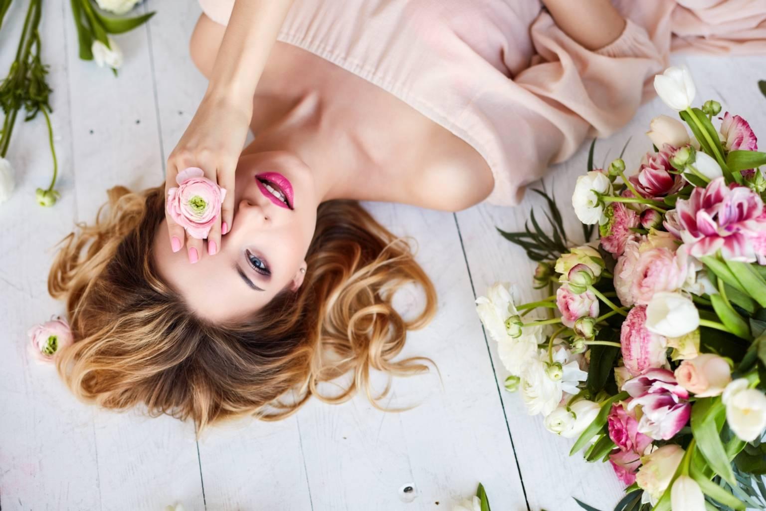 Aromaterapia, czyli leczenie zapachem. Jak działają olejki eteryczne? Piękna kobieta o blond włosach, w jasnej pudrowej sukience leży na podłodze wśród różowych kwiatów i przykłada jeden z nich do oka.