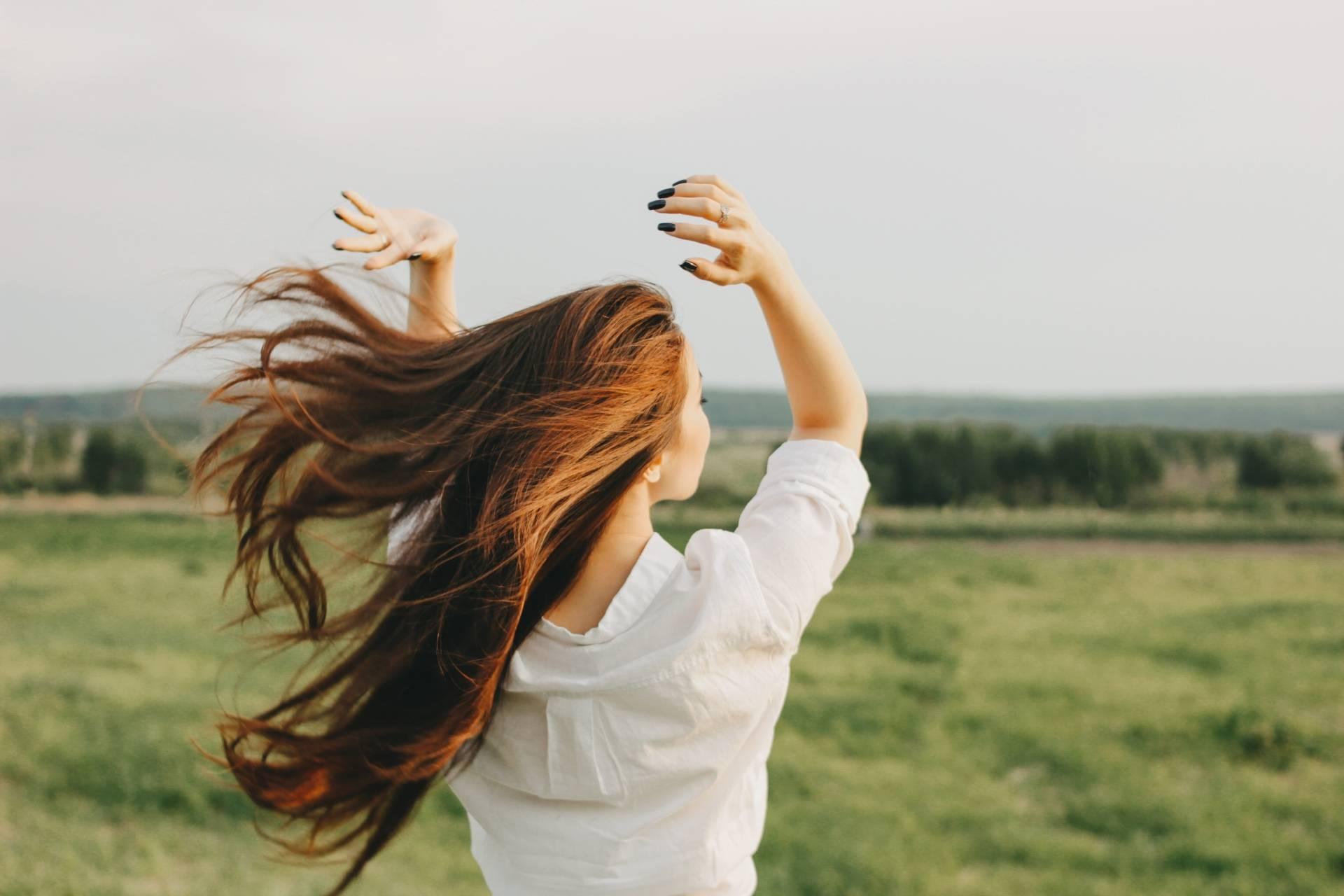 Lachesis mutus - lek homeopatyczny dla kobiet. Rudowłosa kobieta w białej bluzce stoi na polu tyłem do aparatu, a jej włosy rozwiewa wiatr.