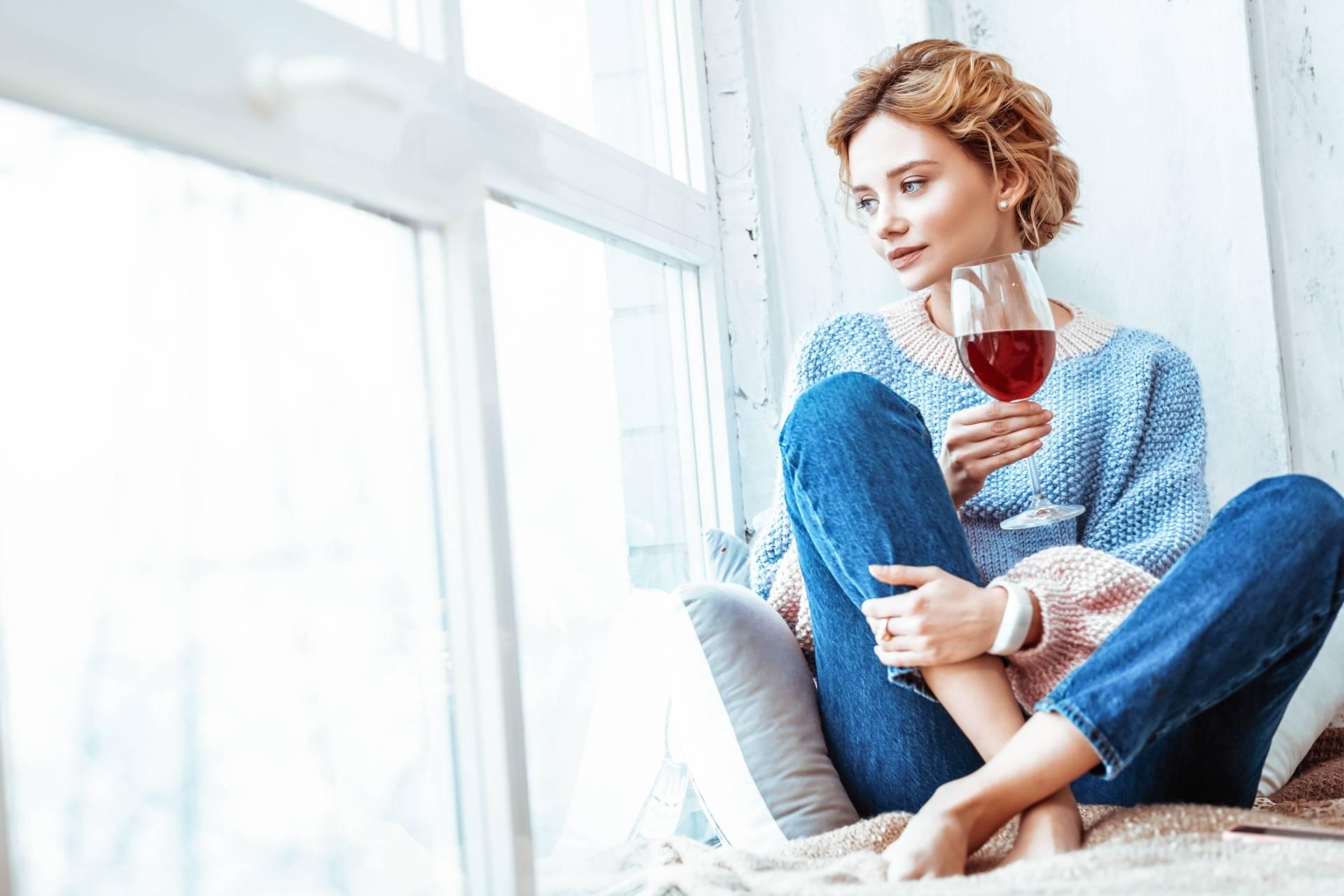 Symptomy kryzysu życiowego. Młoda kobieta siedzi na parapecie z kieliszkiem wina i wpatruje się w widok za oknem.
