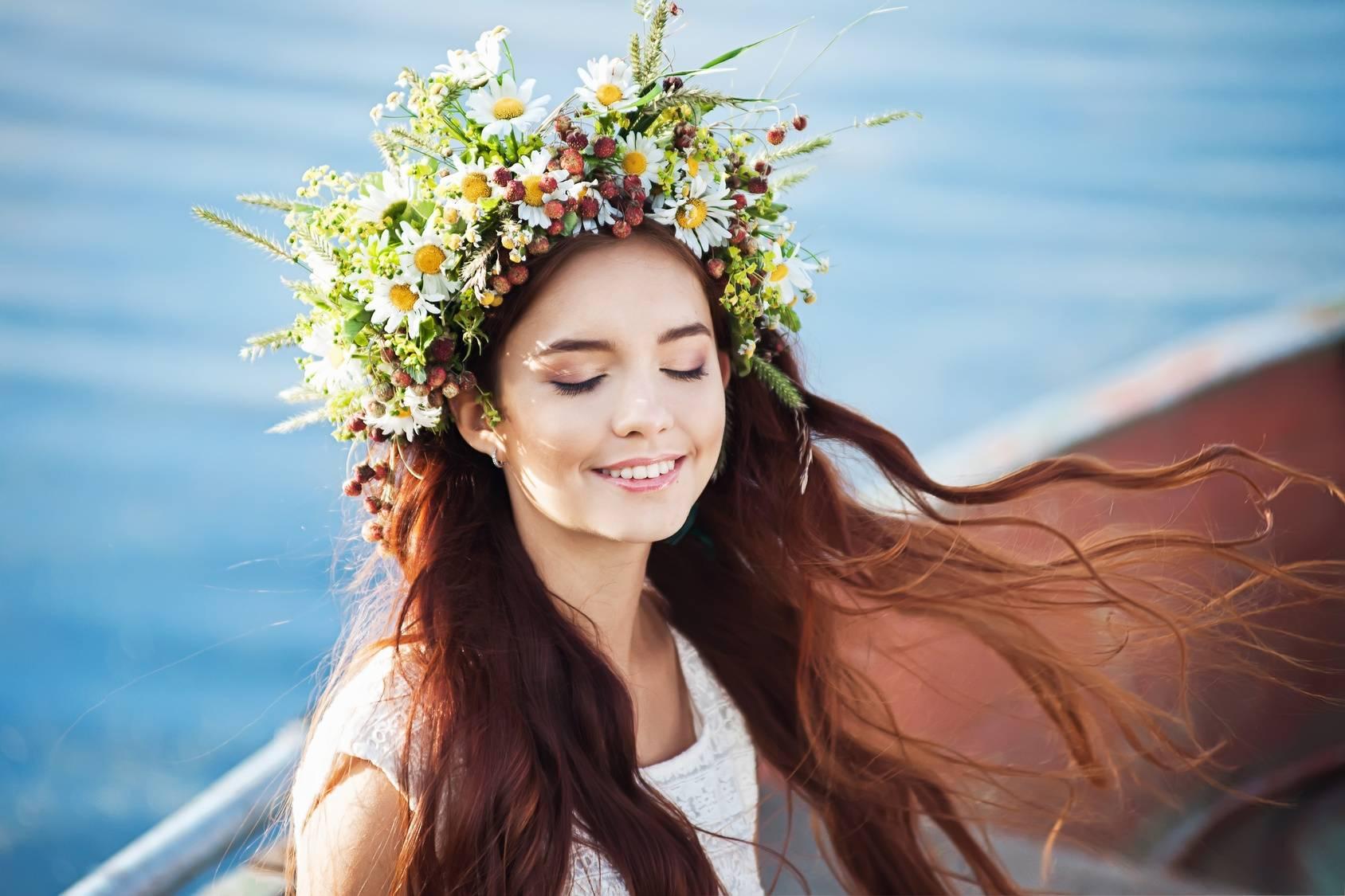 Czym jest alergia? Młoda ciemnowłosa dziewczyna w pięknym, bogato zdobionym wianku z kwiatów siedzi na łodzi i się uśmiecha.