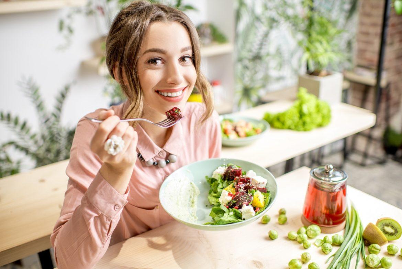 Przewlekłe zaparcia - jakie mogą być przyczyny i jak leczyć? Młoda dziewczyna w różowej bluzce je sałatkę i uśmiecha się do aparatu.