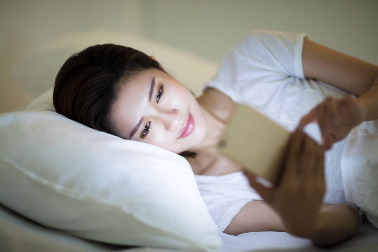 Jak niebieskie światło w ekranach urządzeń elektronicznych wpływa na nasze zdrowie? Kobieta przegląda wiadomości na smartfonie, leżąc wieczorem w łóżku.