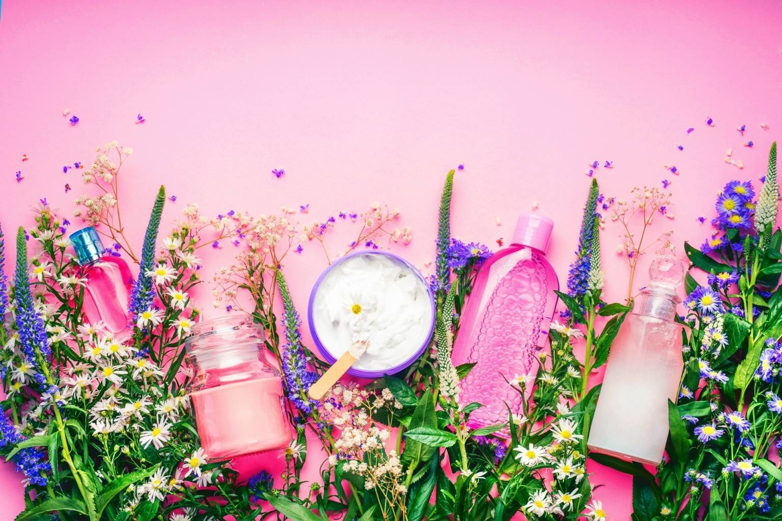 Jak czytać skład kosmetyków? Które substancje zawarte w kremach, lakierach, szamponach czy pastach do zębów są toksyczne i niebezpieczne dla zdrowia? Kosmetyki w kolorowych opakowaniach i kwiaty na różowym tle.