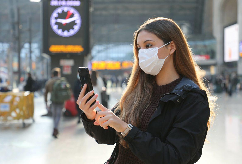 Co wiemy o COVID-19? Sprawdź aktualny stan wiedzy. Dziewczyna w białej masce ochronnej stoi na dworcu i sprawdza informacje w smartfonie.