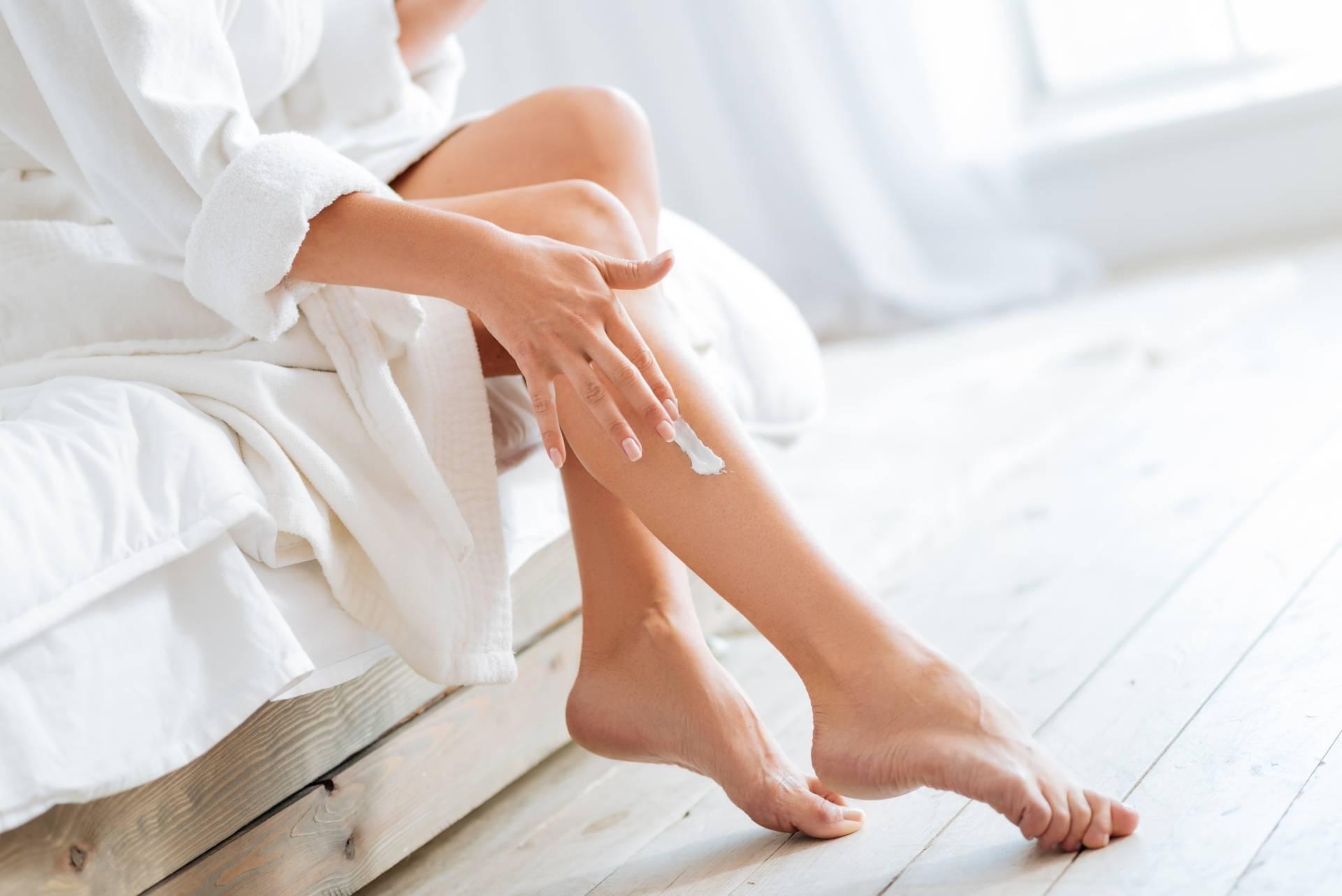 Jakie substancje toksyczne są w składzie popularnych kosmetyków? Kobieta w szlafroku nakłada balsam do ciała na łydkę.
