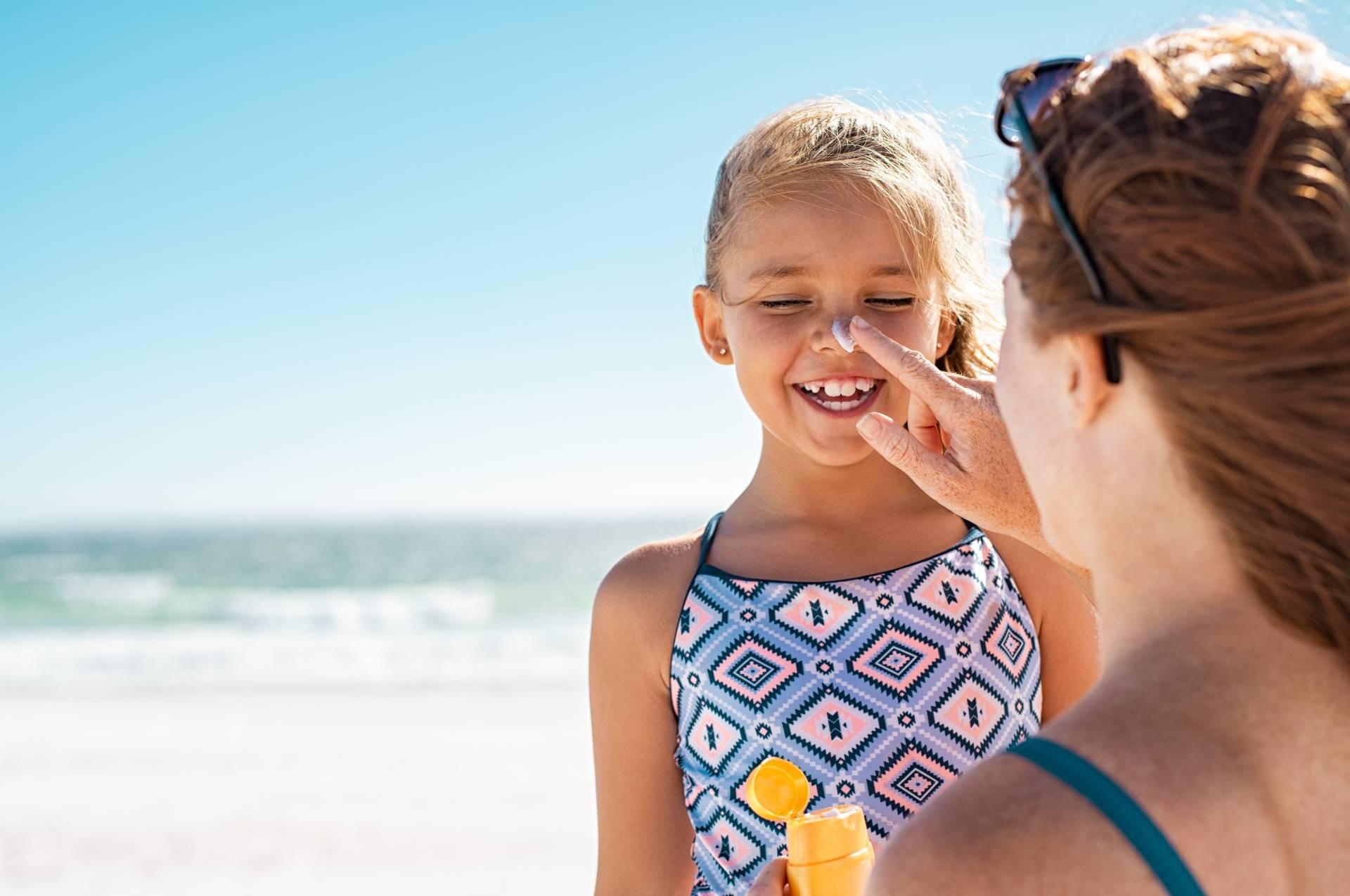 Mama nakłada córce na twarz krem z filtrem.
