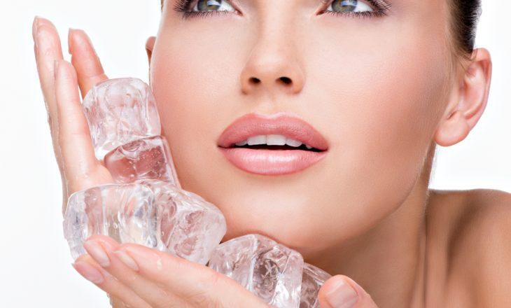 Krioterapia, czyli leczenie zimnem. Kobieta przykłada do twarzy kostki lodu.