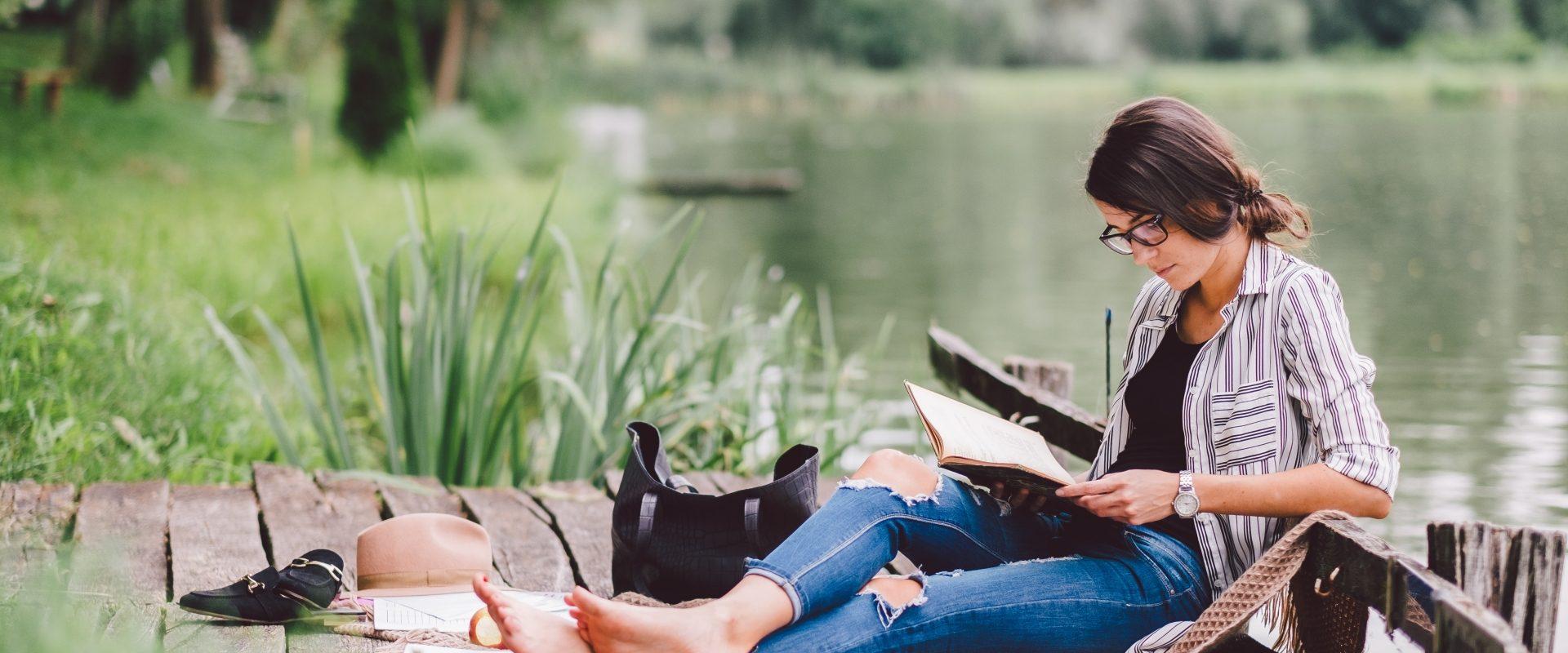 Książki na lato - kobieta w okularach w rogowej oprawce czyta książkę na pomoście nad jeziorem.