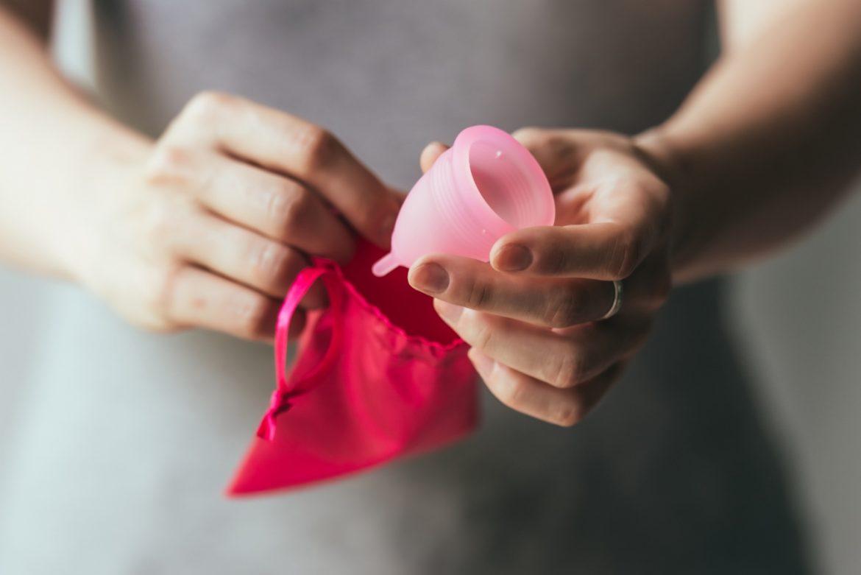 Kubeczek menstruacyjny i podpaski wielorazowe - na czym polega ekologiczna menstruacja? Kobieta w szarej sukience chowa różowy kubeczek do różowego woreczka.