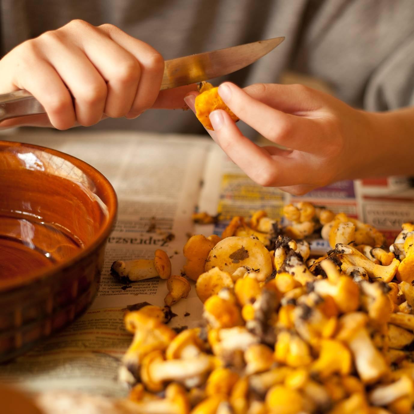 Kurki - przepisy na dania z grzybami. Zbliżenie na kobiece ręce obierające nożykiem kurki nad gazetą.
