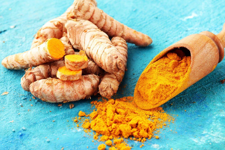 Napój z kurkumy - jak go przygotować? Korzeń kurkumy i sproszkowana kurkuma na drewnianej łyżce leżą na niebieskim blacie.