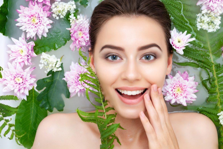 6 kwiatów, które pokocha twoja skóra! Sprawdź, jakie wyciągi z kwiatów najlepiej pielęgnują skórę. Portret kobiety, która bierze kąpiel wśród kwiatów i liści paproci.