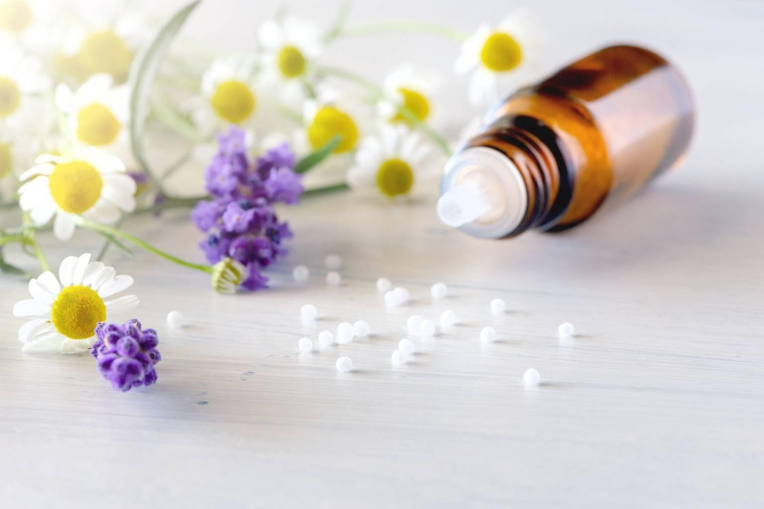 Leki homeopatyczne na dolegliwości w ciąży - granulki rozsypane z fiolki na blacie, obok leżą kwiaty rumianku.