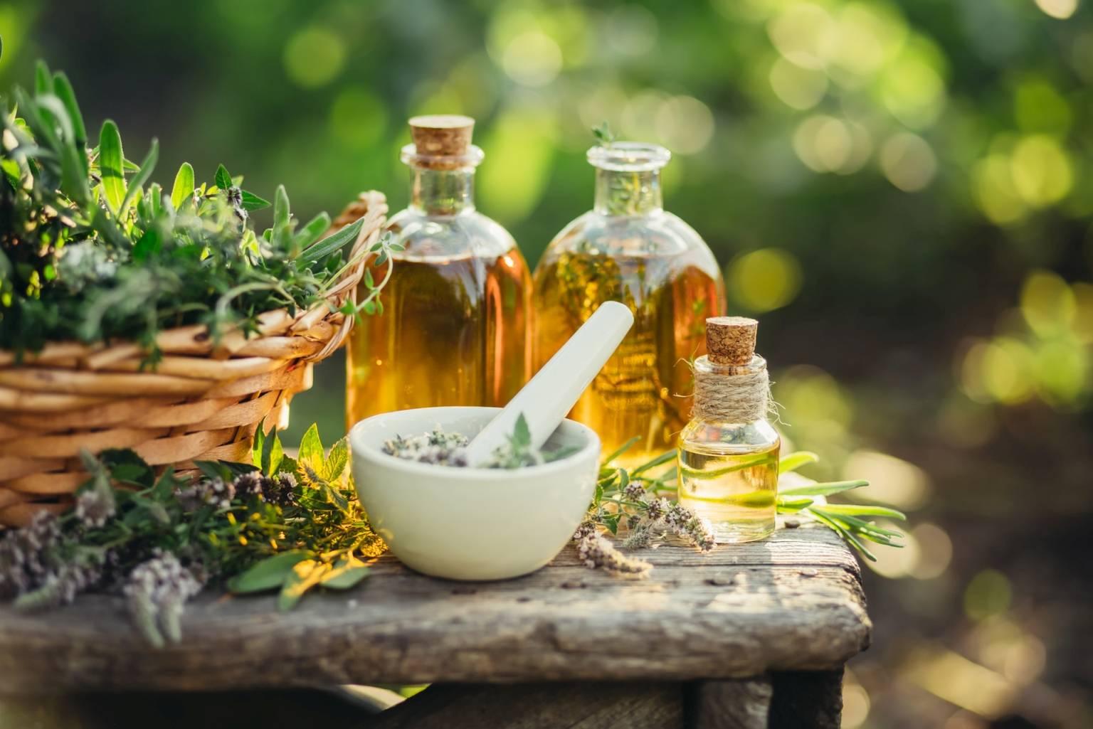 Mieszanki ziołowe na przeziębienie i odporność. Na drewnianym stole w ogrodzie stoją butelki z olejkami, biały moździerz z ziołami i kosz pełen ziół i roślin.