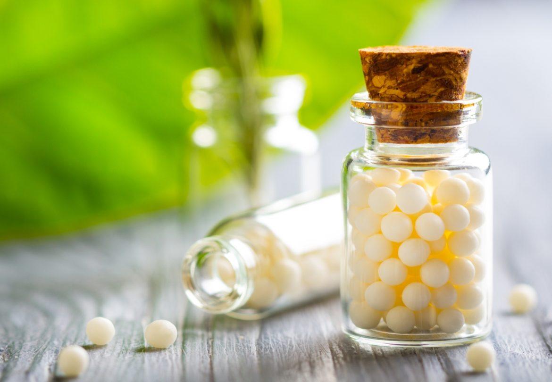 Lek homeopatyczny Magnesia phosphorica pomaga na skurcze. Fiolki granulek homeopatycznych na blacie, w tle leży zielony liść.