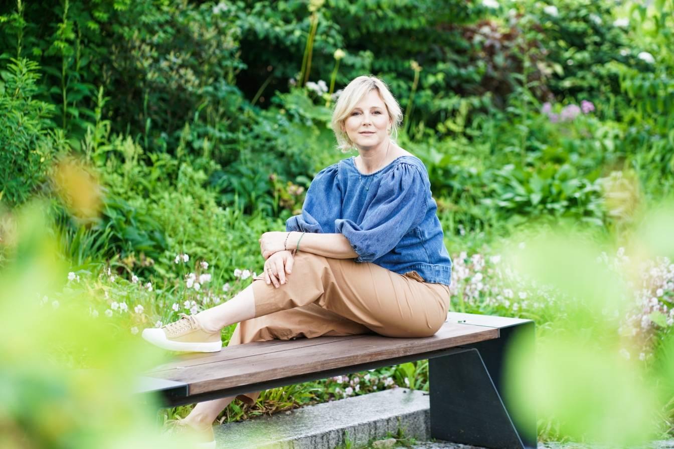 Maja Popielarska siedzi na ławce w ogrodzie.